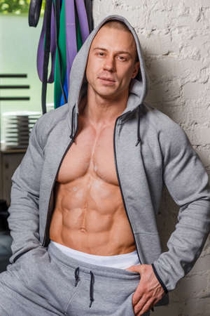 pectorals: Strong muscular man bodybuilder poses and shows his body