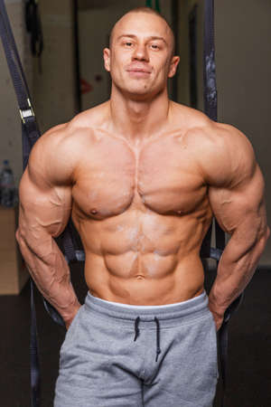 earnest: Strong muscular man bodybuilder poses and shows his muscles Stock Photo