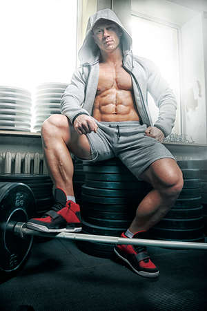 cheekbones: Strong muscular man bodybuilder sits on barbell plates Stock Photo