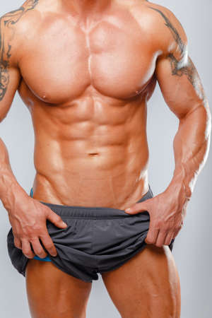 beefcake: Strong muscular man bodybuilder poses and shows his muscles Stock Photo