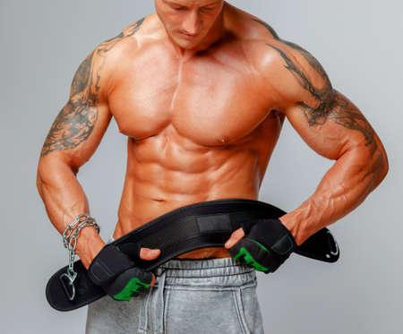 pezones: Hombre musculoso fuerte posa mostrando su cuerpo y la celebración de la correa de alimentación