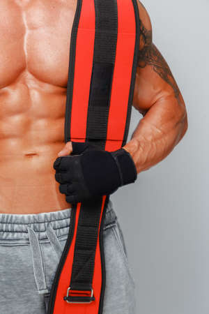 beefcake: Strong muscular man poses and shows body holding power belt