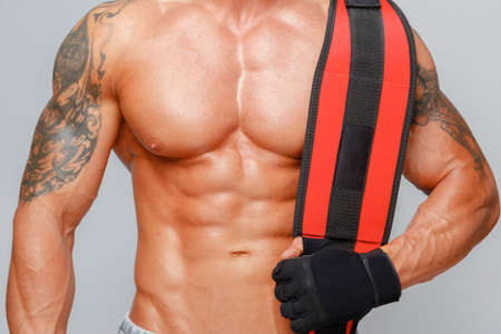 beefcake: Muscular man showing his abs and holding power-belt
