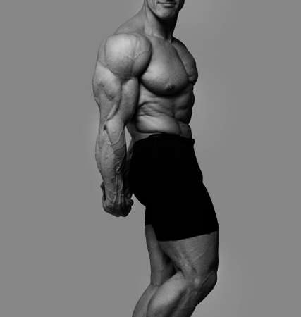 Portrait of muscle man posing in grey background photo