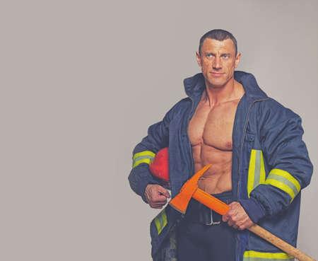 Portrait of fireman posing on grey background photo