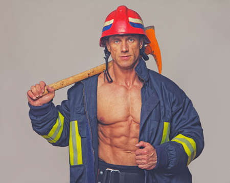 fireman: Portrait of fireman on grey background Stock Photo