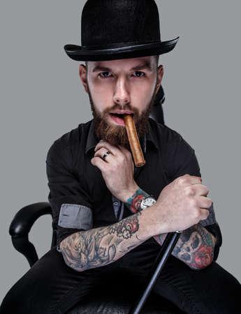 tattoed: Masculino Tattoed sentado en silla de cuero con ca�a en la mano Foto de archivo
