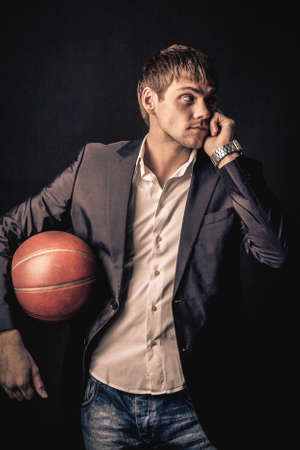celling: Young man holding basketball ball and celling by the phone Stock Photo