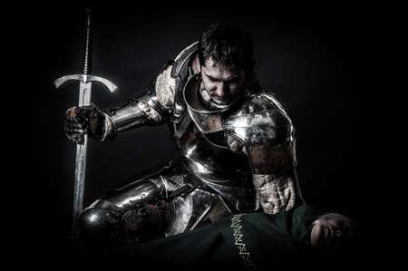 死んでいる暗殺者を見ての騎士 写真素材