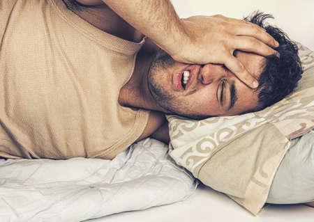Homem novo na cama, tentando dormir