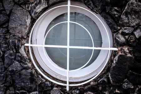 White porthole in the stone wall photo