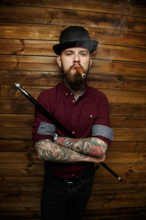 Brutal man with tattooes and hat on his had smoking holding walking stick