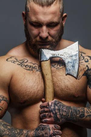hombre desnudo: Enorme macho brutal con la barba y tatooes sosteniendo el hacha