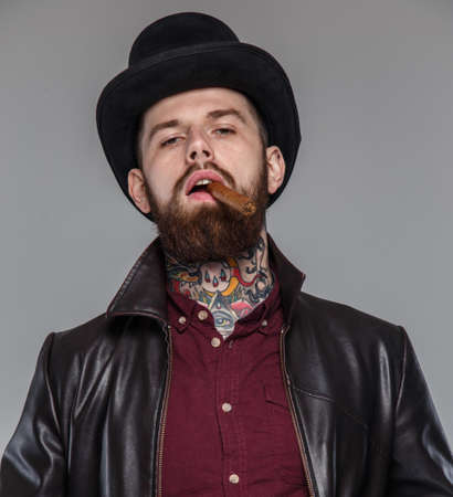 tattoed: Tattoed male with cigar in his mouth Stock Photo