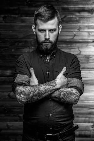 Brutal tattooed man with full seriousness look
