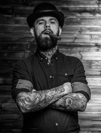 Portrait of brutal tattooed male smoking cigar