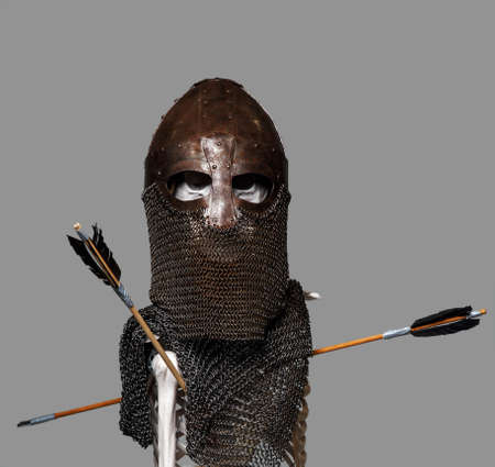 Skeleton of the dead warrior in the helmet and chain armour with arrows in his body photo