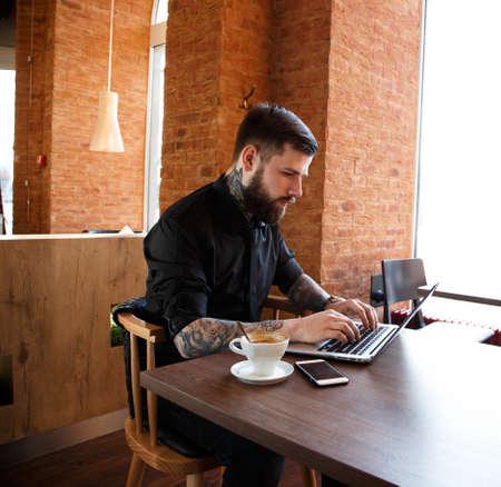 hombre tomando cafe: Hombre serio con tatuajes que trabajan en un ordenador port�til en una cafeter�a