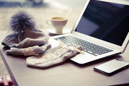 pompon: Woolen hat with pompon and mitten near a laptop and cup of coffe on the wooden table