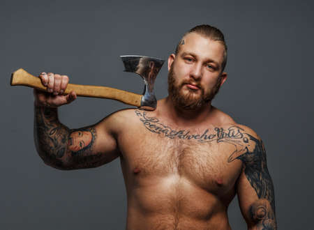 naked male body: Huge brutal male with beard and tatooes holding axe
