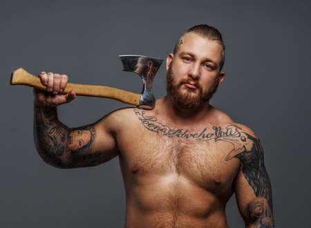 homme nu: Immense m�le brutal avec barbe et tatooes tenant une hache