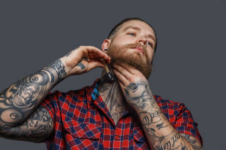 brutal: Huge brutal man with tattoo shawing his beard with a razor Stock Photo