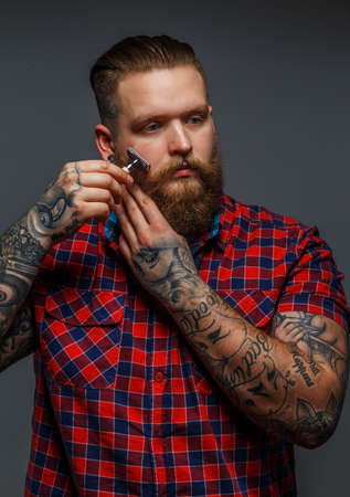 Huge brutal man with tattoo shawing his beard with a razor Stock Photo