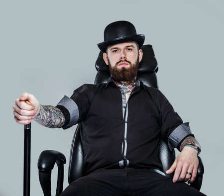 cane chair: Serious gangster in hat sitting on leather chair holding cane