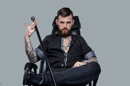 Serious man holding cane sitting on leather chair