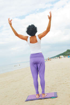 yoga pants: Middle age woman with shirt black hair in a white t-shirt and purple pants doing yoga on the summer beach.