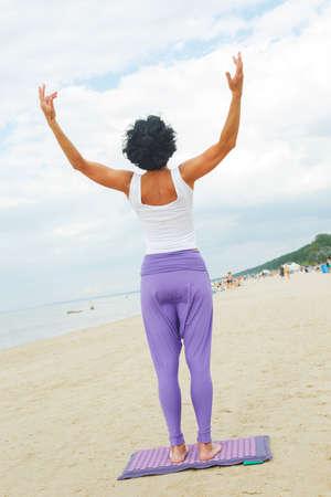 černé vlasy: Středního věku žena s černými vlasy košile v bílé tričko a fialové kalhoty dělá jógu na pláži v létě.