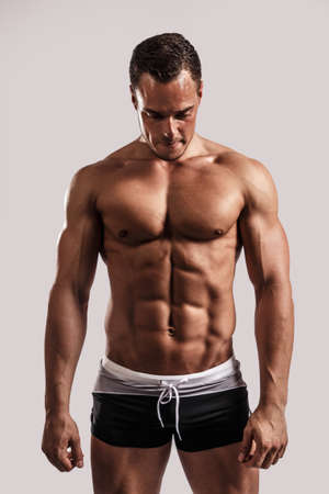Portrait of a handsome muscular man in black beach shorts isolated on white in studio. photo