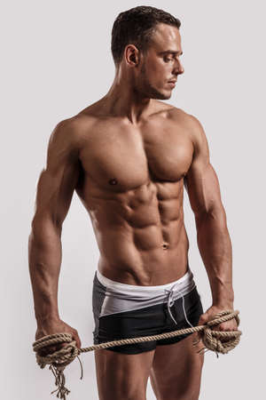Portrait of a handsome muscular man in black beach shorts with rope in his hand isolated on white in studio. photo