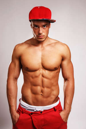Portrait in studio of muscular male in red sport pants with white stripe on them and a red cap. Isolated on grey background.