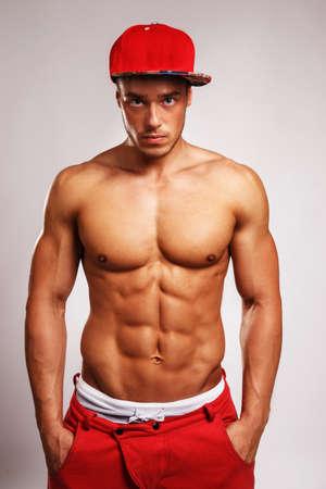 desnudo masculino: Retrato en estudio de masculino muscular en pantalones de deporte de color rojo con franja blanca en ellos y una gorra roja. Aislado en el fondo gris.