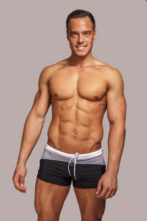 naked abs: Young guy with great body anatomy in black swim shorts possing in studio. Light grey background.