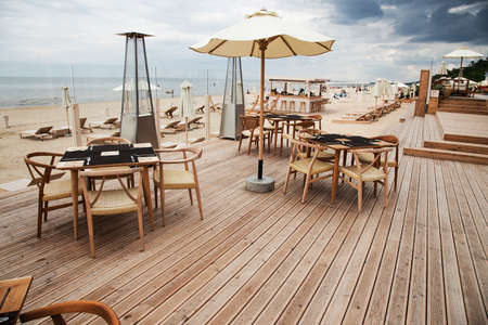 sun umbrellas: Summer terrace for relaxation  on  open air in the summer beach with wooden chairs, tables, sofas and sun umbrellas.