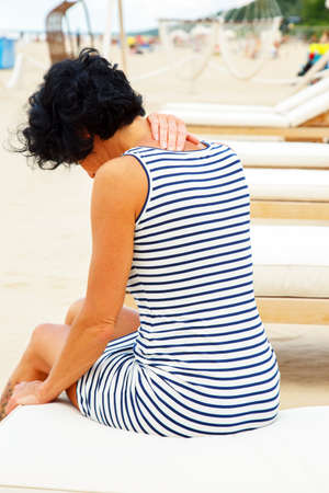heaving: Middle age woman with black hair in striped dress sitting on a beach sofa and heaving backache. Stock Photo