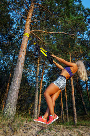 tough woman: Tough young woman in sports clothink doing fitness in the forest. Pine trees and blue sky on the background. Stock Photo