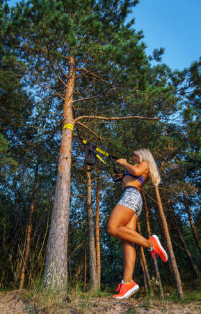jungle gyms: Tough young woman in sports clothink doing fitness in the forest. Pine trees and blue sky on the background. Stock Photo