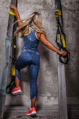 view from behind: Awesome blond female in leopard sportswear and  gym shoes posing between two columns after her exercises. View from behind.