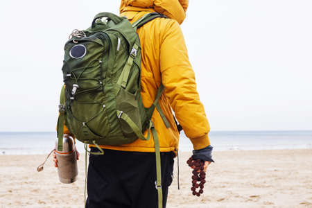 yellow jacket: Man dressed in black pants and yellow jacket from behind with green backpack stands on winter beach.