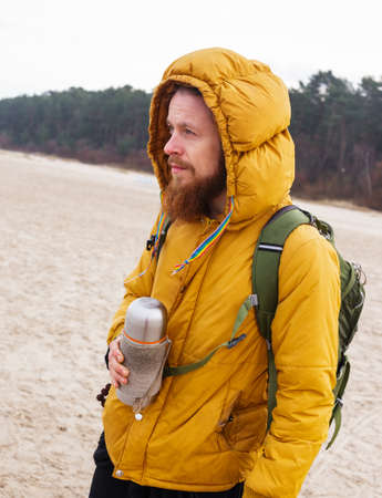 black pants: Man with beard dressed in yellow jacket and black pants hold thermon. Winter seashore. Forest on background.