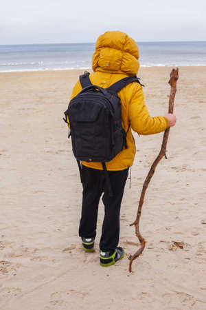 outspread: Man from behind dressed in yellow jacket with black backpack, hold stich, stands on the winter beach.