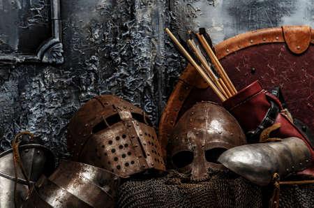 medieval: Armaduras Brown. Dos cascos, flechas, escudos y armaduras sobre fondo gris.