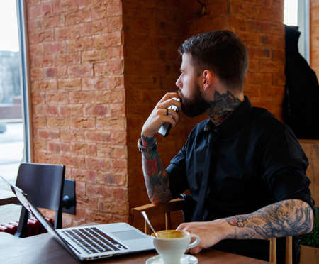 tattoed: Tattoed man with beard work with laptop during a lunch.
