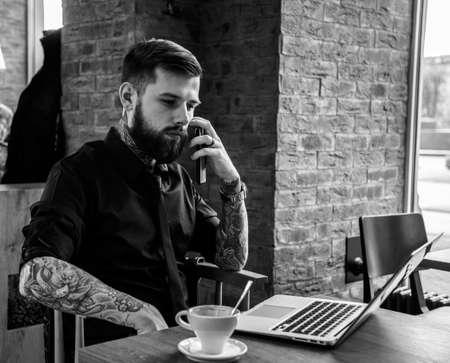 tattoed: Tattoed hombre con barba de trabajo con ordenador port�til durante un almuerzo.