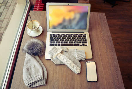 White open laptop with coffee cup, mobile phone, mittens and winter cap on wooden table in a cafe. Stock Photo