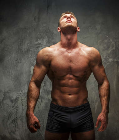 naked male body: Muscular man with great body relief watching up on white light. Grey background. Stock Photo