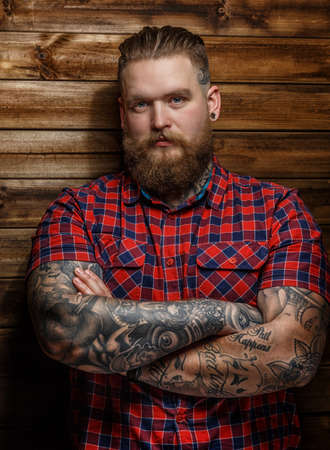 beefcake: Huge brutal man with beard and tattooes Stock Photo